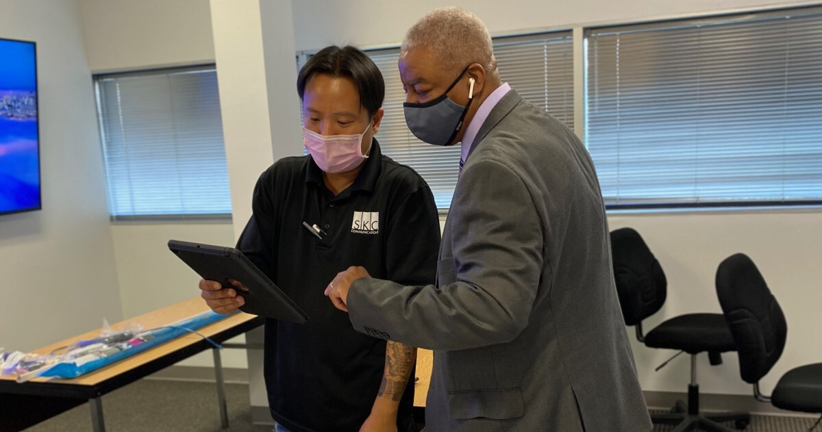 Two people stand with masks on looking at a tablet