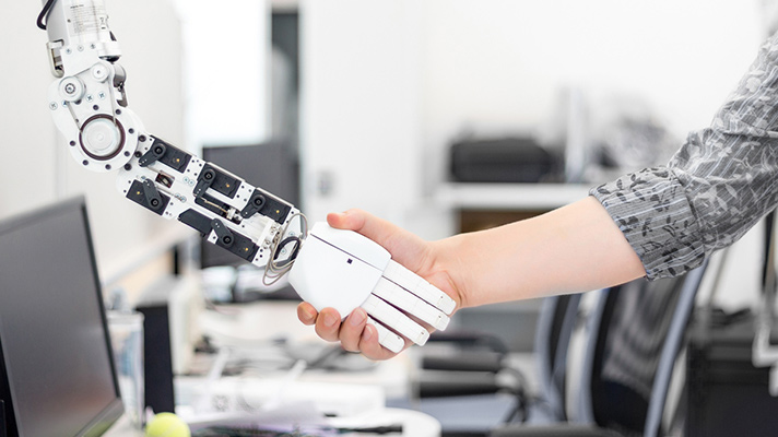 Human shakes hands with robot symbolizing big data.