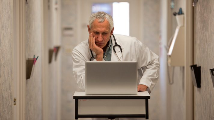 Frustrated doctor at a computer.