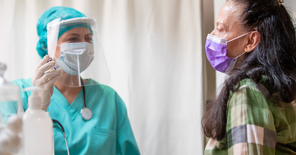 Doctor in PPE with patient in mask