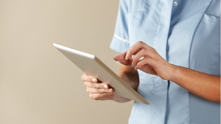 Clinician using tablet in UK hospital.