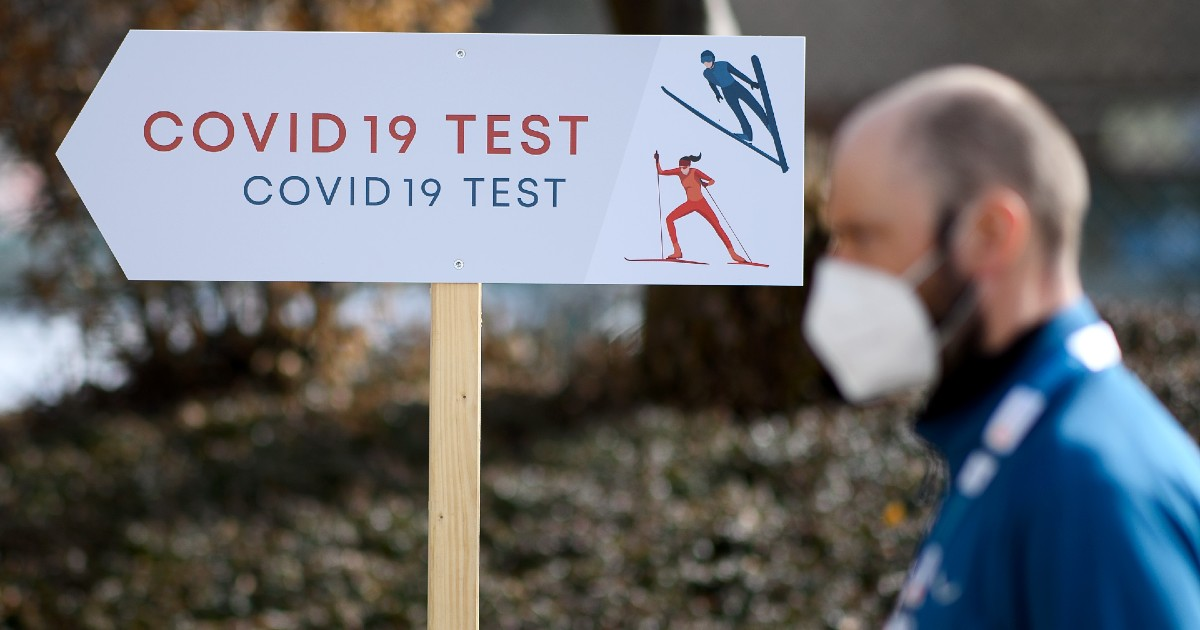 A person stands in front of a COVID-19 test sign