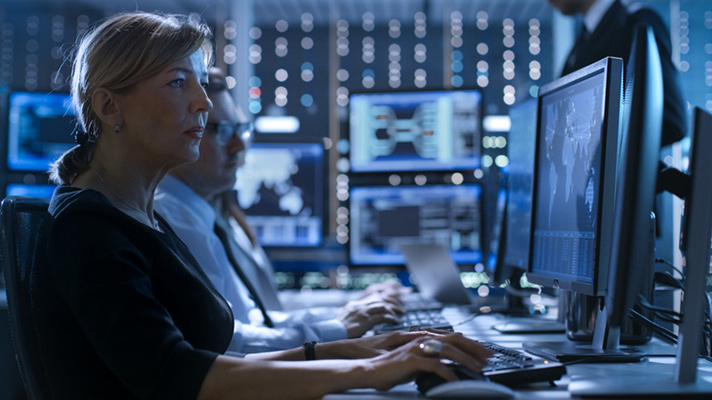 Cybersecurity employees in a control room.