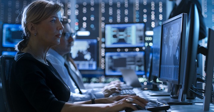 A person sits in a darkened room in front of a wall of computers