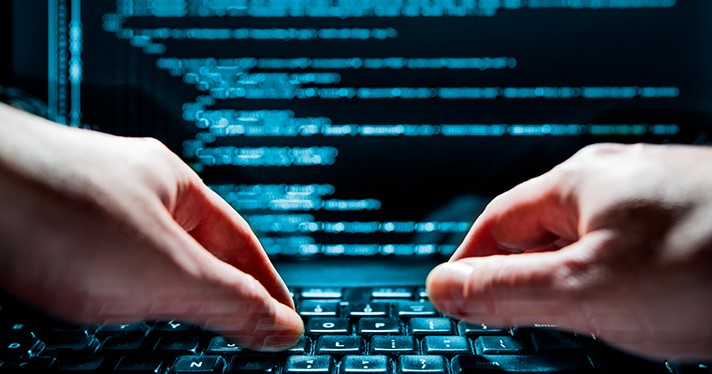 Hands on a keyboard before a computer screen