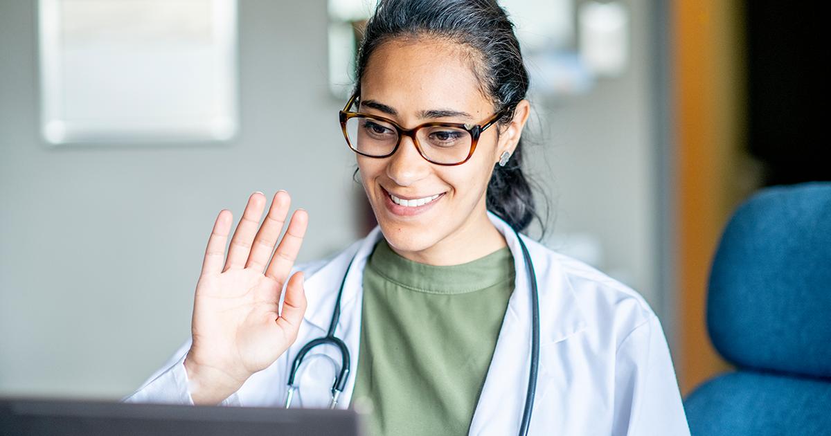 Person in medical garb doing a virtual visit via telehealth