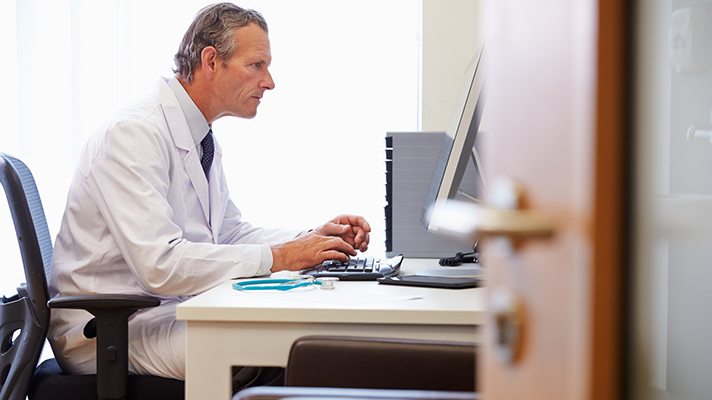 EHR doctor at a desktop computer