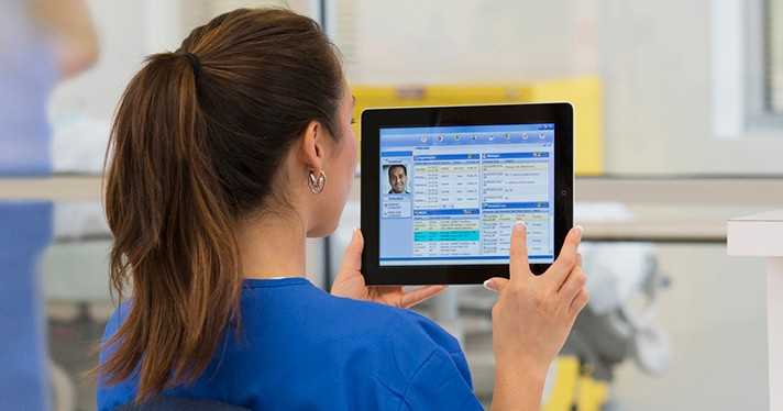 A person in scrubs with a ponytail holds up a tablet