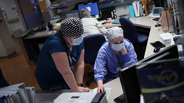 Two people wearing scrubs and masks at a computer