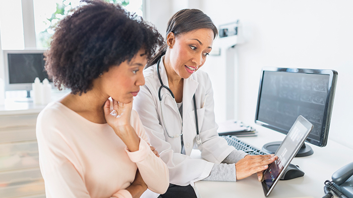 Doctor helping consumer with medical record.