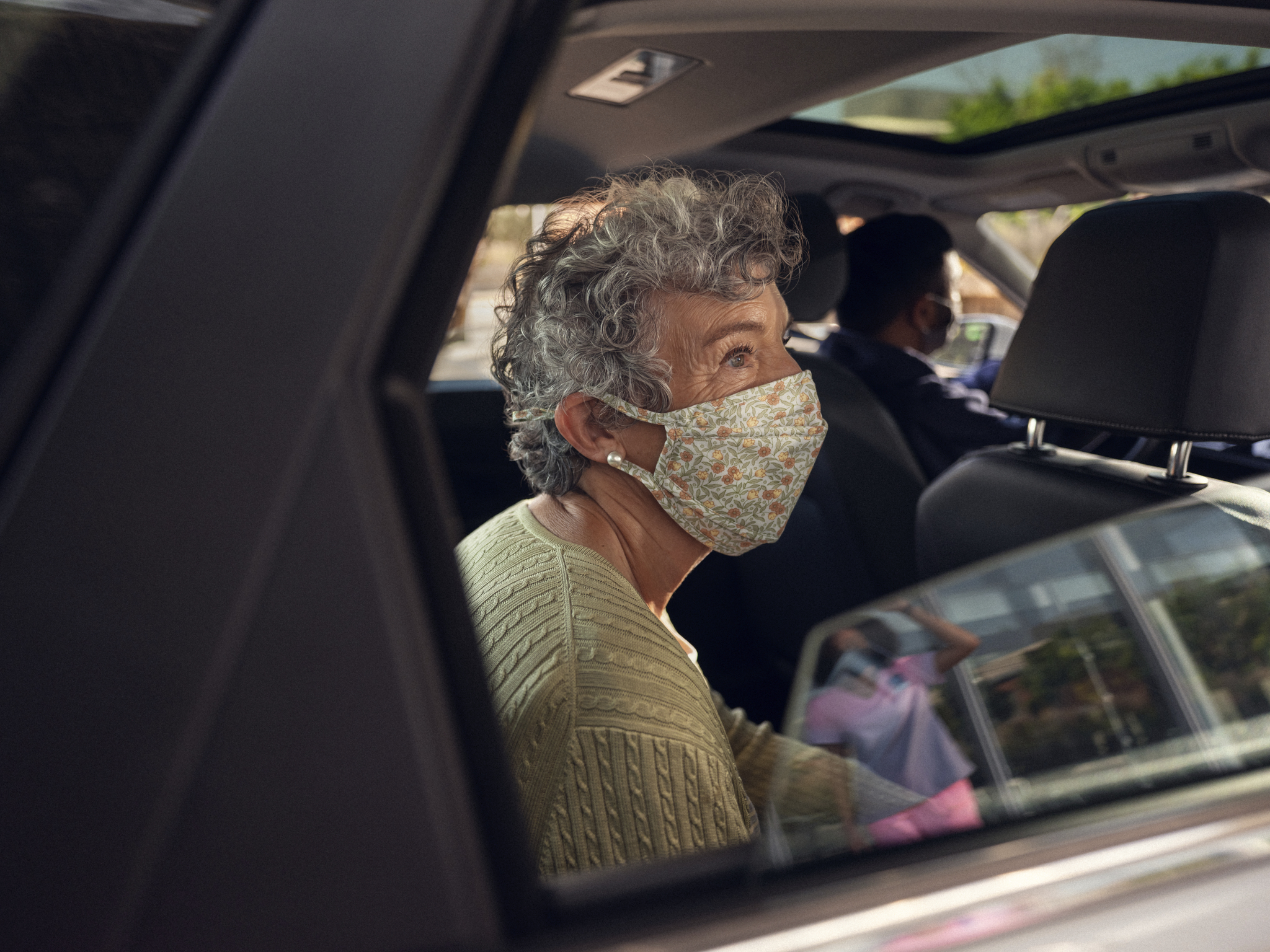 A passenger wearing a mask in the backseat of a car