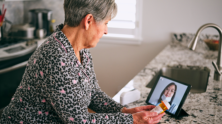 A woman looks at a medication bottle with a person onscreen.