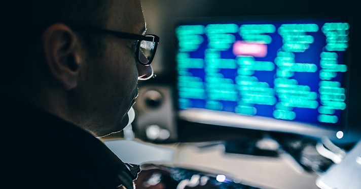 A cybersecurity expert sits in a darkened room in front of a computer screen