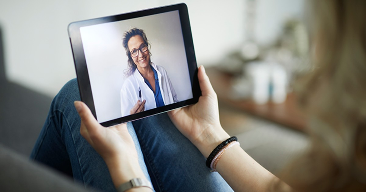 A physician visible on a tablet screen