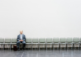 Businessman alone in row of empty chairs