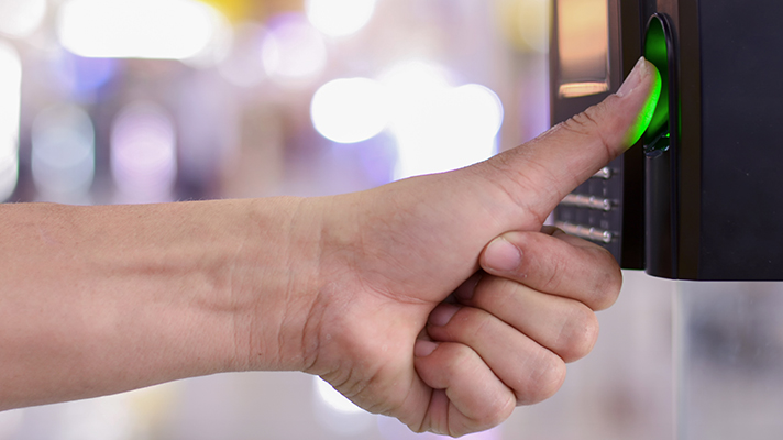 man putting thumb on biometric reader