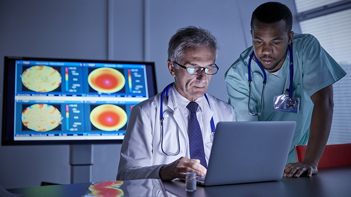 doctor and nurse looking at xrays on computer screen