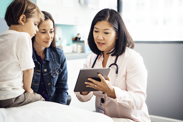 Doctor looking at tablet with patient