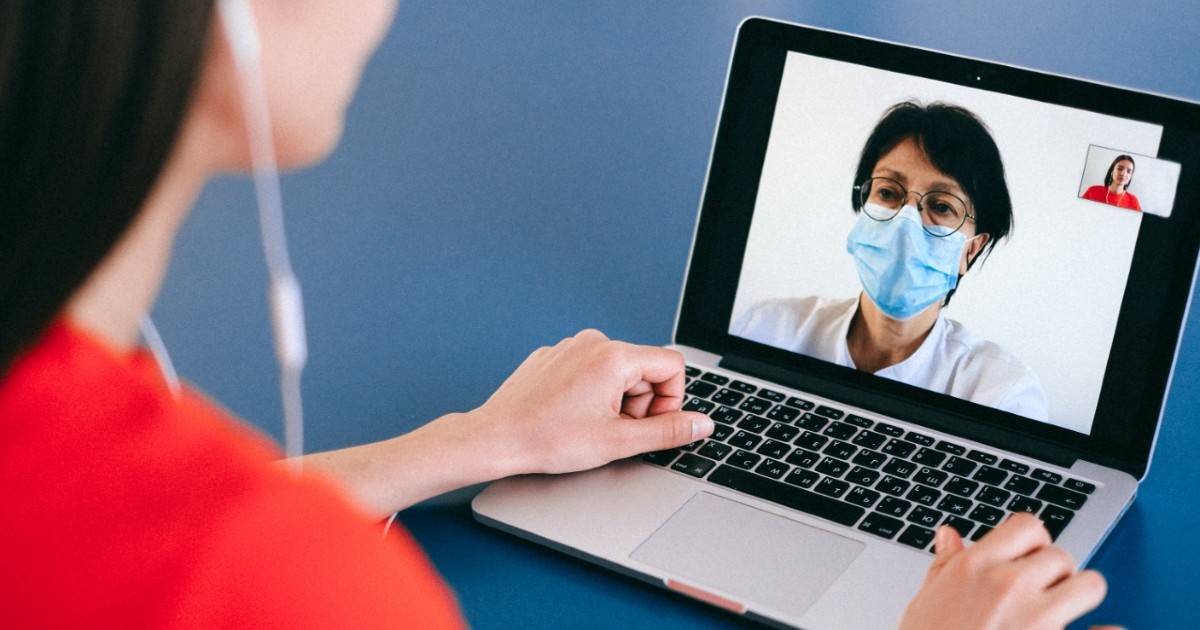 A patient speaks to a doctor on a computer
