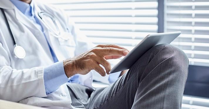 Doctor resting EHR-enabled tablet on knee