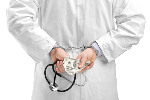 doctor in handcuffs holding money
