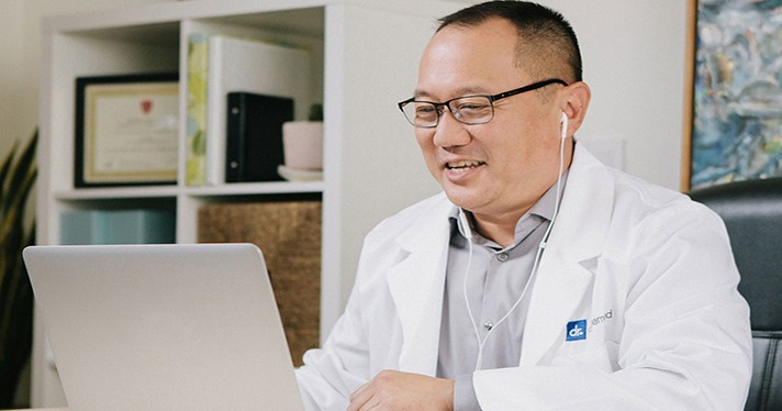 Doctor On Demand physician smiling at laptop