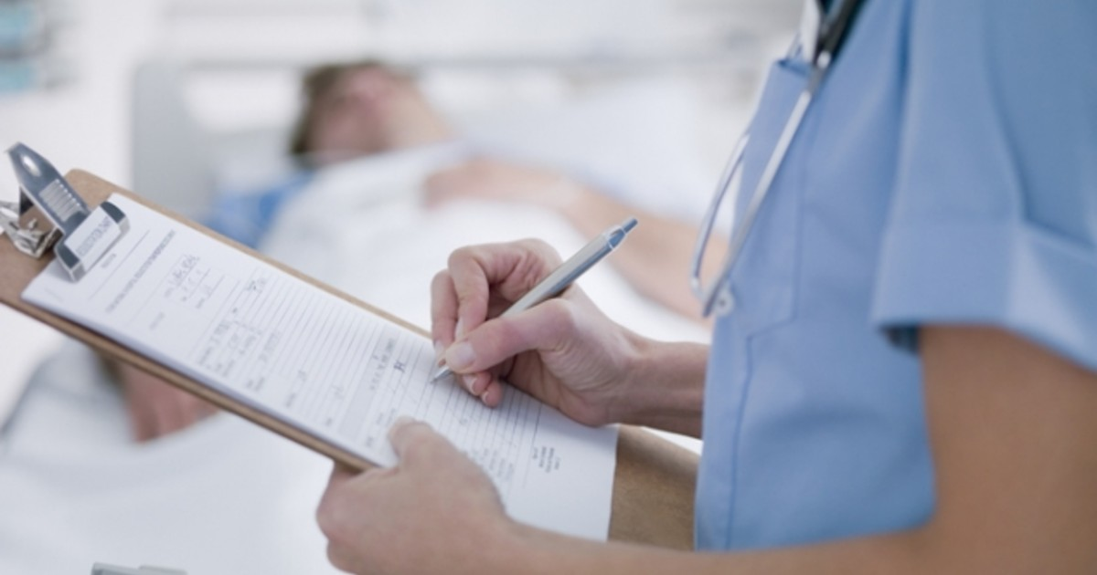 A person in medical wear holds a paper document on a clipboard