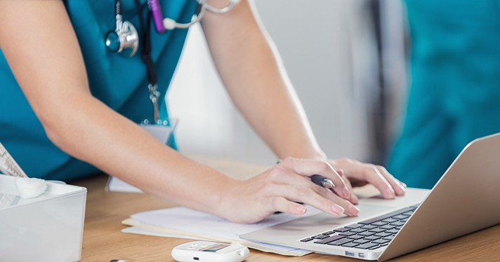 A person wearing stethoscope uses a laptop.