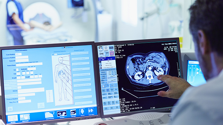 doctor looking at imaging results on a computer screen