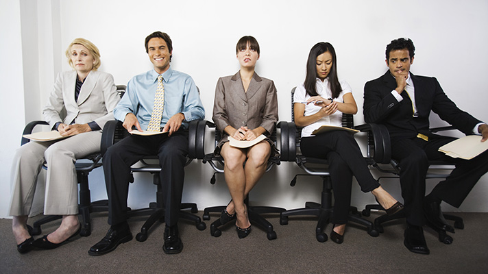 workers sitting in a row waiting for job interview