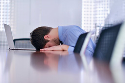 Stressed man placing head and hands on table