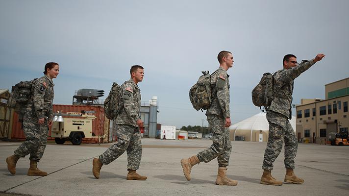 US military troops walking across airfield