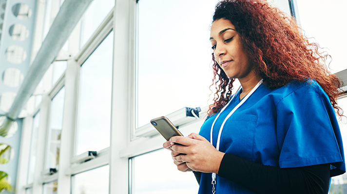 nurse texting on phone in hospital