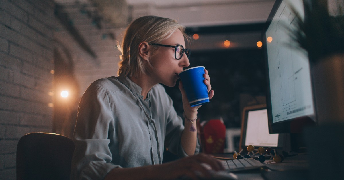 A person drinking coffee in front of a computer screen