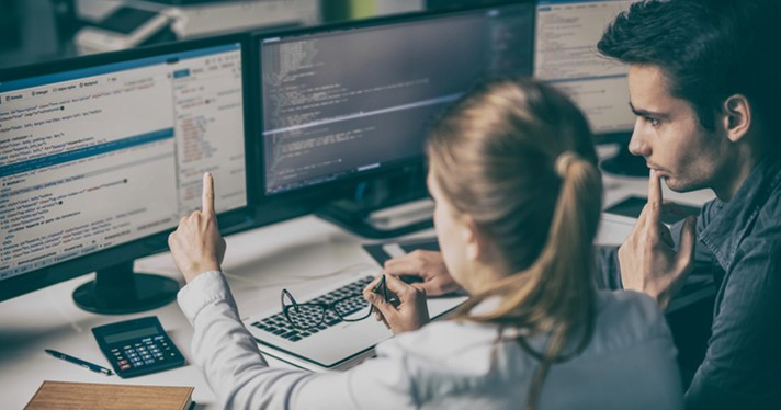 People in office studying computer screens for malware