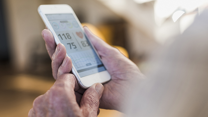 smartphone health app screen held by older person
