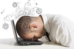 Stressed man with head on laptop