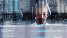 Man working with computer code around him.