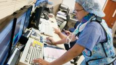 person in PPE at computer, health IT