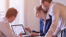 Group of businesspeople looking at a laptop