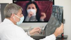 Doctor in mask doing teleconference
