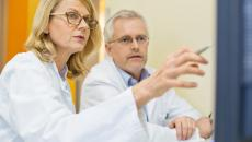 doctors discussing risk science at computer screen