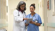 A person wearing a stethoscope pointing at a tablet that a person in scrubs is holding