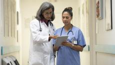 doctor and nurse discuss EHR issues in clinical setting
