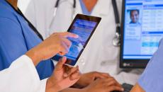 A doctor holds a tablet with an EHR on it