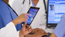 doctor working on EHR tablet, computer