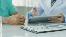 doctor with patient looking at tablet health record
