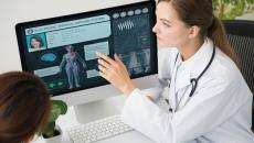 Doctor pointing to electronic medical record on a screen