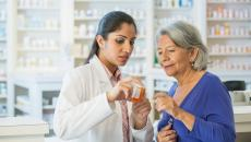 Pharmacist assisting senior customer.