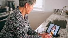 A patient looks at a doctor's face on a tablet screen
